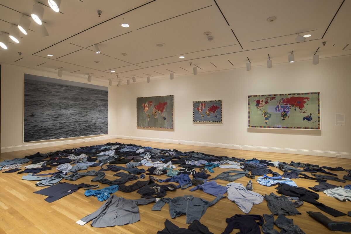 """Installation view of """"The Warmth of Other Suns,"""" with embroidered maps by Alighiero Boetti against the back wall; Kader Attia's Le Mer Morte ( The Dead Sea ), 2015; and a photograph by Wolfgang Tillmans, titled The State We're In , 2015. Photo by Lee Stalsworth. Courtesy of the Phillips Collection."""