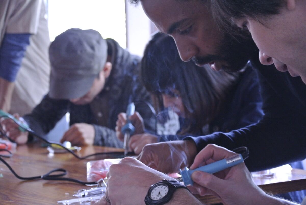 Johann Diedrick helps his students build their mobile listening kits at Social Kitchen in Kyoto, Japan.