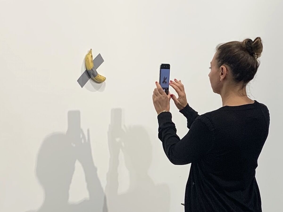 A visitor to Art Basel in Miami Beach photographs Comedian (2019) by Maurizio Cattelan in the Perrotin booth. Photo by Benjamin Sutton.