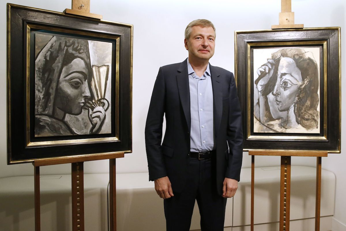 Russian businessperson and President of French football club AS Monaco Dmitry Rybolovlev poses in Paris on September 24, 2015 in front of two allegedly stolen paintings by Pablo Picasso, Espagnole a l'Eventail (left) and Femme se Coiffant (right), which he purchased from a Swiss art dealer. Photo by Patrick Kovarik/AFP via Getty Images.