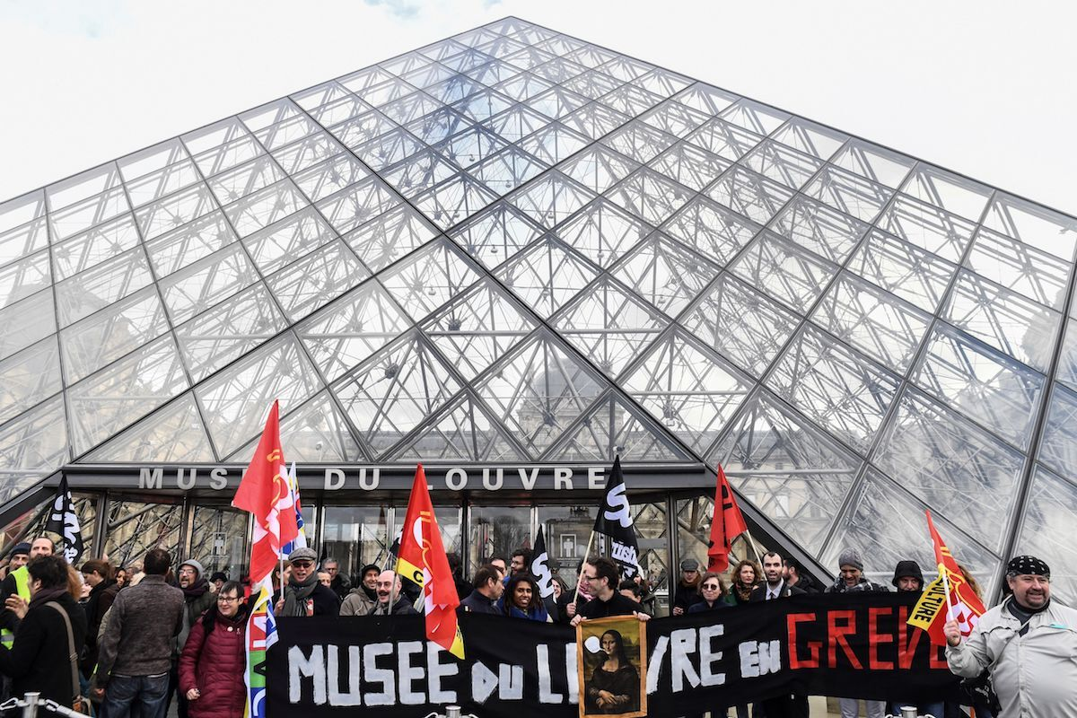"""Protesters outside the iconic pyramid designed by I.M. Pei  at the Louvre museum hold a banner that reads, in French: """"Louvre Museum on Strike."""" Photo by Alain Jocard/AFP via Getty Images."""
