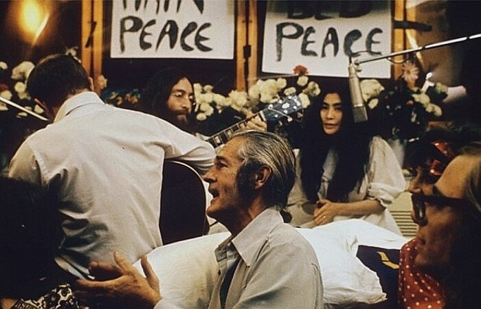 """Left to right: Rosemary Leary (face not visible), Tommy Smothers (with back to camera), John Lennon, Timothy Leary, Yoko Ono, Judy Marcioni, and Paul Williams recording """"Give Peace a Chance,"""" 1969."""