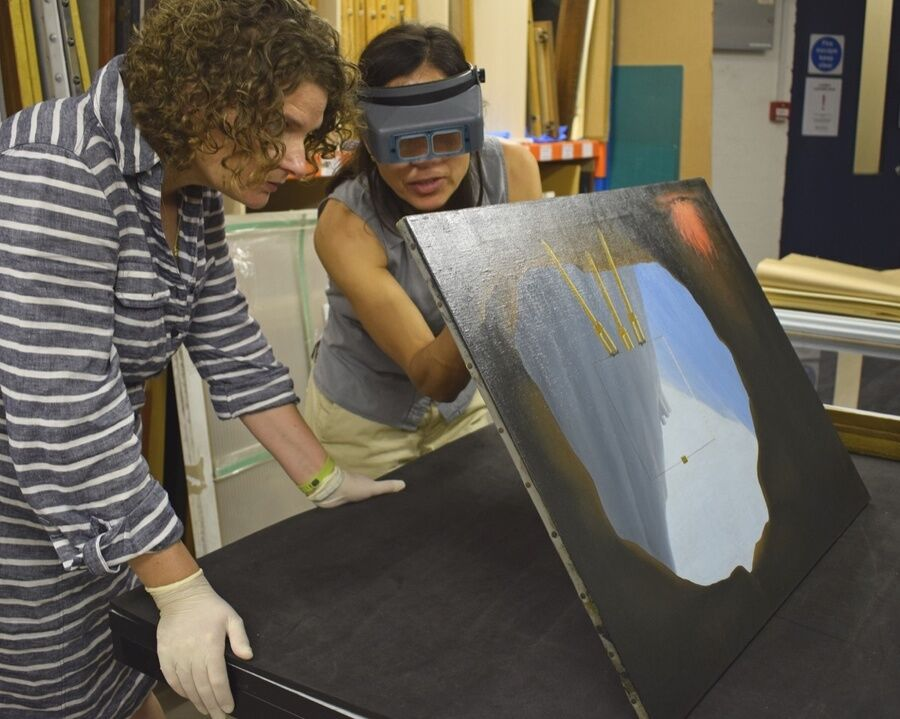 Curator of Historic Art at Norwich Castle Giorgia Bottinelli (left) and conservator Alice Tavares da Silva examine Magritte'sLa Condition Humaine.© Norfolk Museums Service.