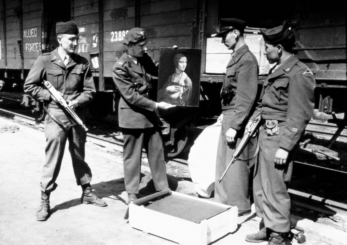 Monuments Man Lt. Frank P. Albright, Polish Liaison Officer Maj. Karol Estreicher, Monuments Man Capt. Everett Parker Lesley, and Pfc. Joe D. Espinosa, guard with the 34th Field Artillery Battalion, pose with Leonard da Vinci's Lady with an Ermine upon its return to Poland in April 1946. Photo courtesy the Monuments, Fine Arts, and Archives program, via Wikimedia Commons.