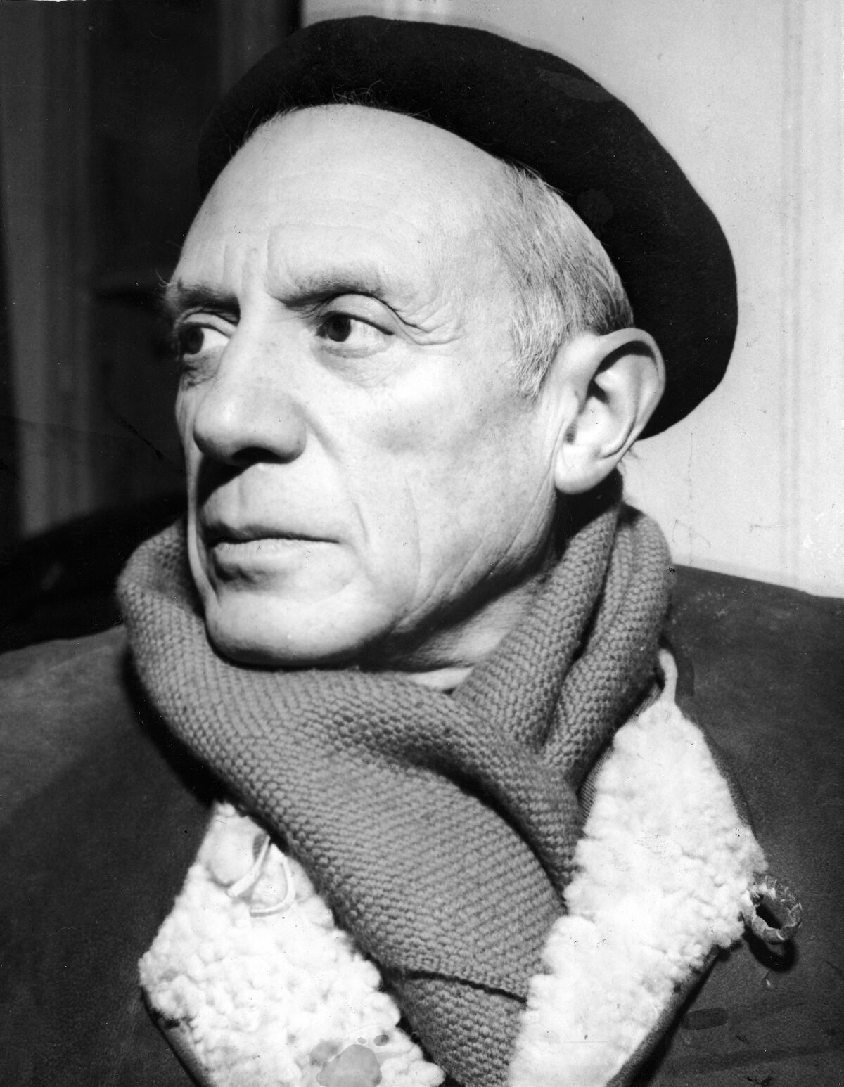 Portrait of Pablo Picasso in a winter coat, scarf, and beret, ca. 1950s. Photo by Hulton Archive/Getty Images.