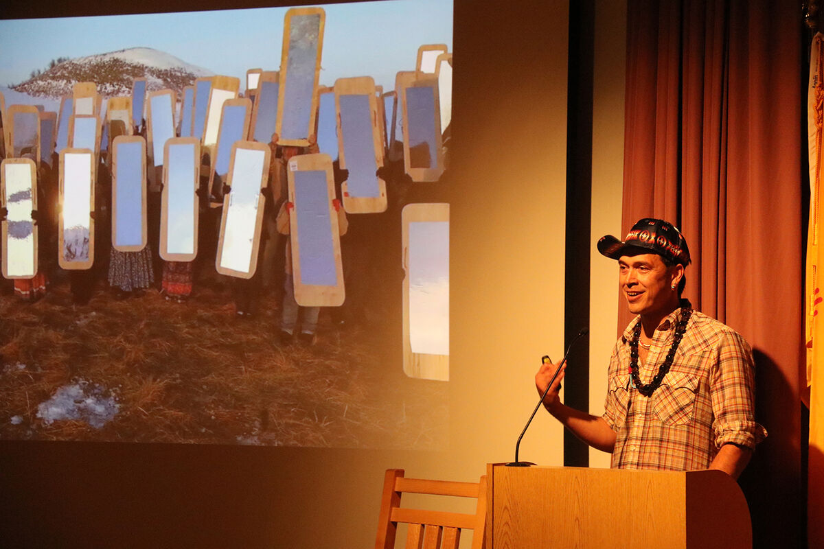 """Portrait of Cannupa Hanska Luger (Mandan, Hidatsa, Arikara, Lakota) presenting his Mirror Shield Project in """"Environmental Collapse: Native Perspectives on the Land, Protection and Stewardship"""" during the Southwestern Association for Indian Arts (SWAIA) 98th Annual Santa Fe Indian Market, August 2019. Courtesy of Native Arts and Cultures Foundation."""