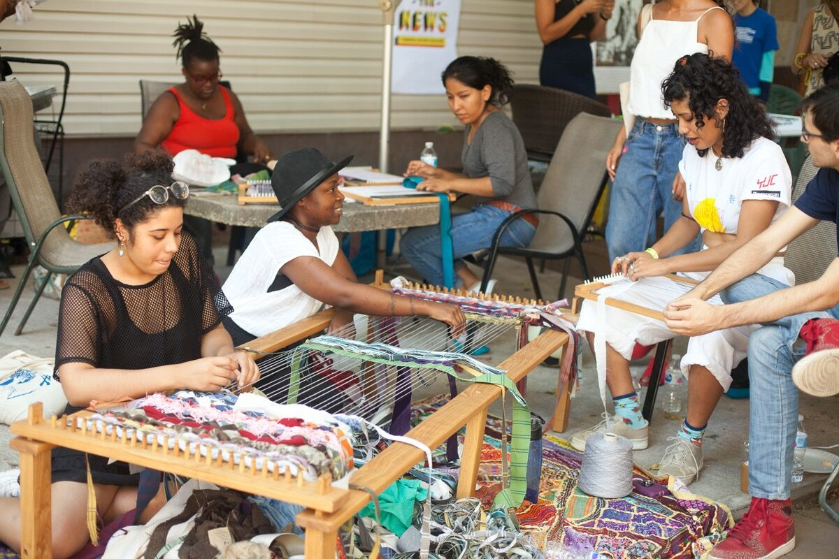 Neighbors weave together as part of a workshop facilitated by Weaving Hand and organized by 2017 Create Change Bed-Stuy Fellows during The Laundromat Project's Bed-Stuy Field Day Festival in Hancock Community Garden, 2017. Photo by Neha Gautam. Courtesy of The Laundromat Project.