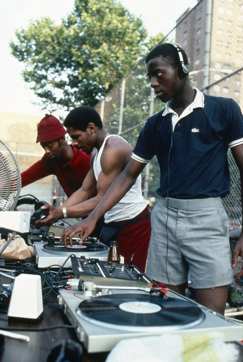 Henry Chalfant, Dez, Gman, and Friend Prepare for a Park Jam, 144th and 3rd Ave., The Bronx, 1984. © 2018 Henry Chalfant / Artists Rights Society (ARS), New York. Courtesy Eric Firestone Gallery, New York.