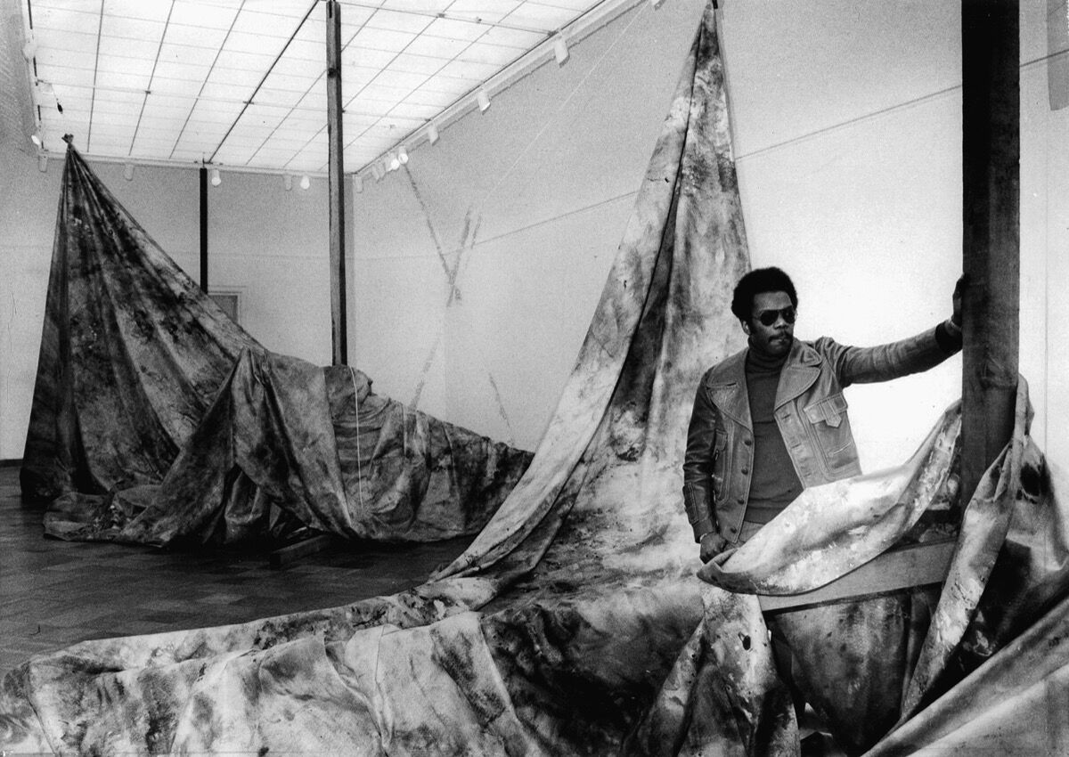 Sam Gilliam with his work, Autumn Surf , at the San Francisco Museum of Modern Art, 1973. © Sam Gilliam. Photo by Art Frisch. Courtesy of San Francisco Chronicle/Polaris.