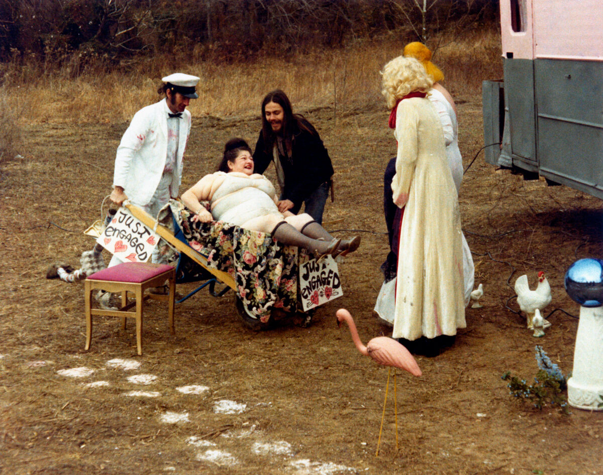 American actor Paul Swift carrying American actress and singer Edith Massey on a barrow in the film Pink Flamingos. American actors Danny Mills and Mary Vivian Pearce attending the scene. 1972. Photo by Mondadori Portfolio via Getty Images.