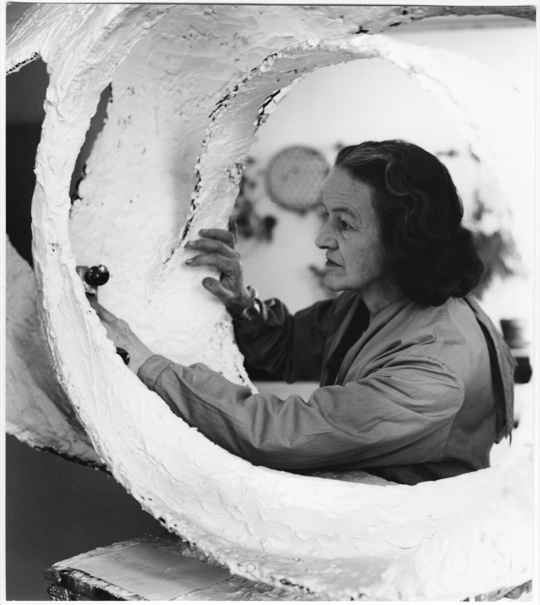 """Barbara Hepworth at work on the plaster for Oval Form (""""Trezion""""), 1963. Photo by Val Wilmer. © Bowness, Hepworth Estate. Courtesy of the Hepworth Wakefield."""