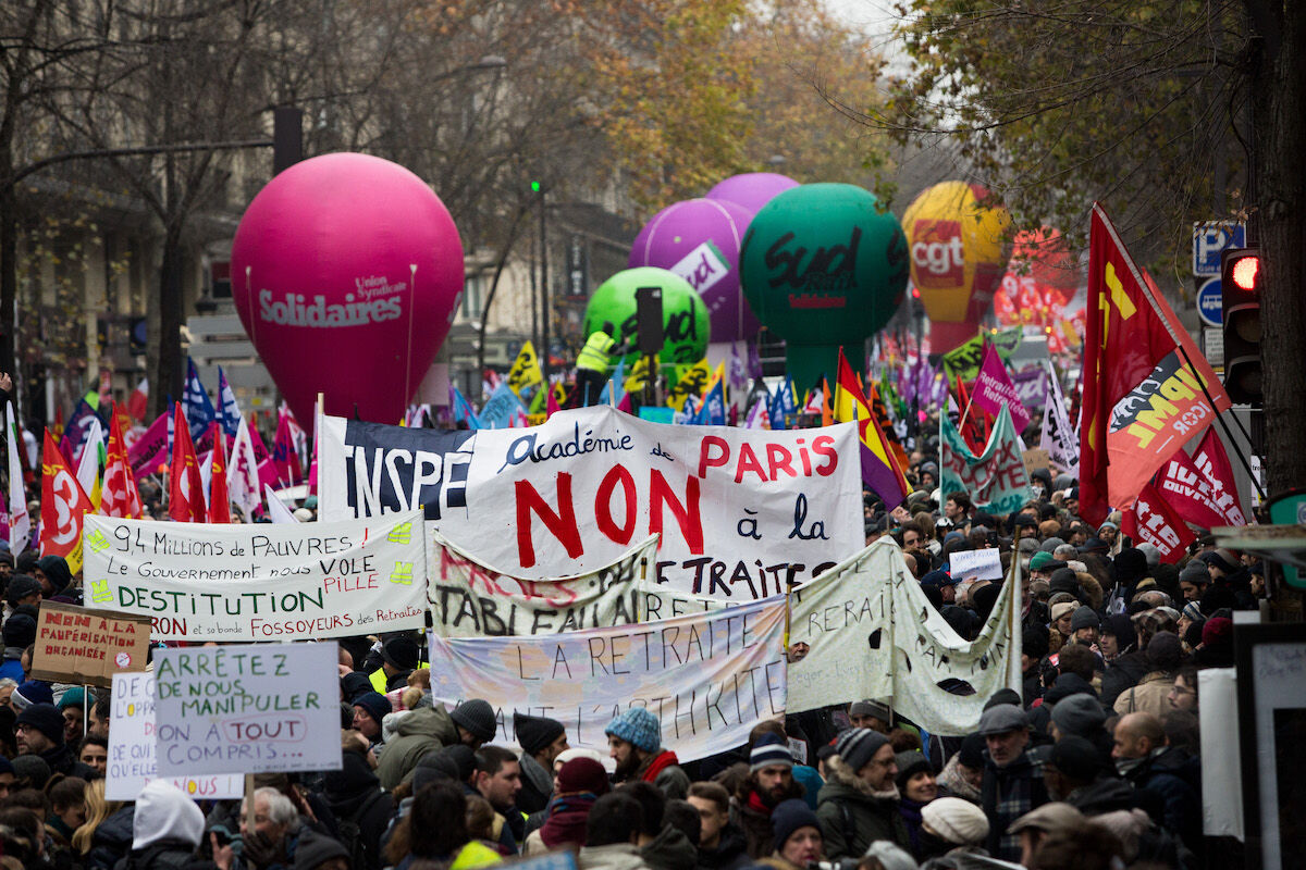 Protesters march in Paris against government pension reform plans and in defense of public service. Photo by Emeric Fohlen/NurPhoto via Getty Images.