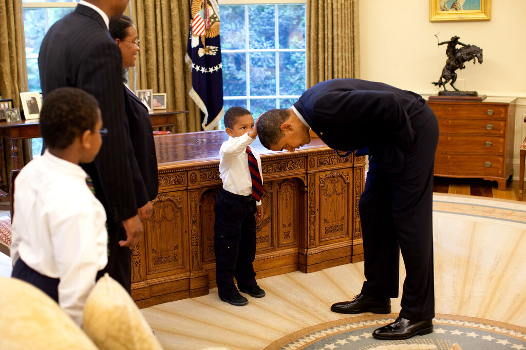 President Barack Obama bends over so the son of a White House staff member can pat his head during a family visit to the Oval Office, 2009. Photo by Pete Souza. Courtesy of the White House Photo Office via Flickr.