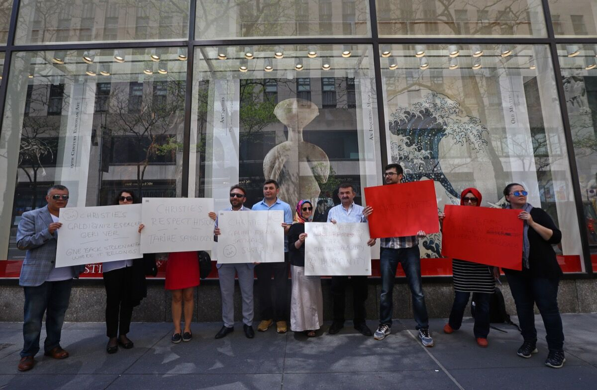 Turkish people hold placards during a protest in front of the Christies Auction House after one of best examples of Kiliya-type Anatolian marble female idols Ancient Anatolian Guennol Stargazer statue, which dates back to the third millennium BC, was sold at an auction about 14,5 millions dollars in New York, United States on April 28, 2017. Photo: Anadolu Agency/ Getty.