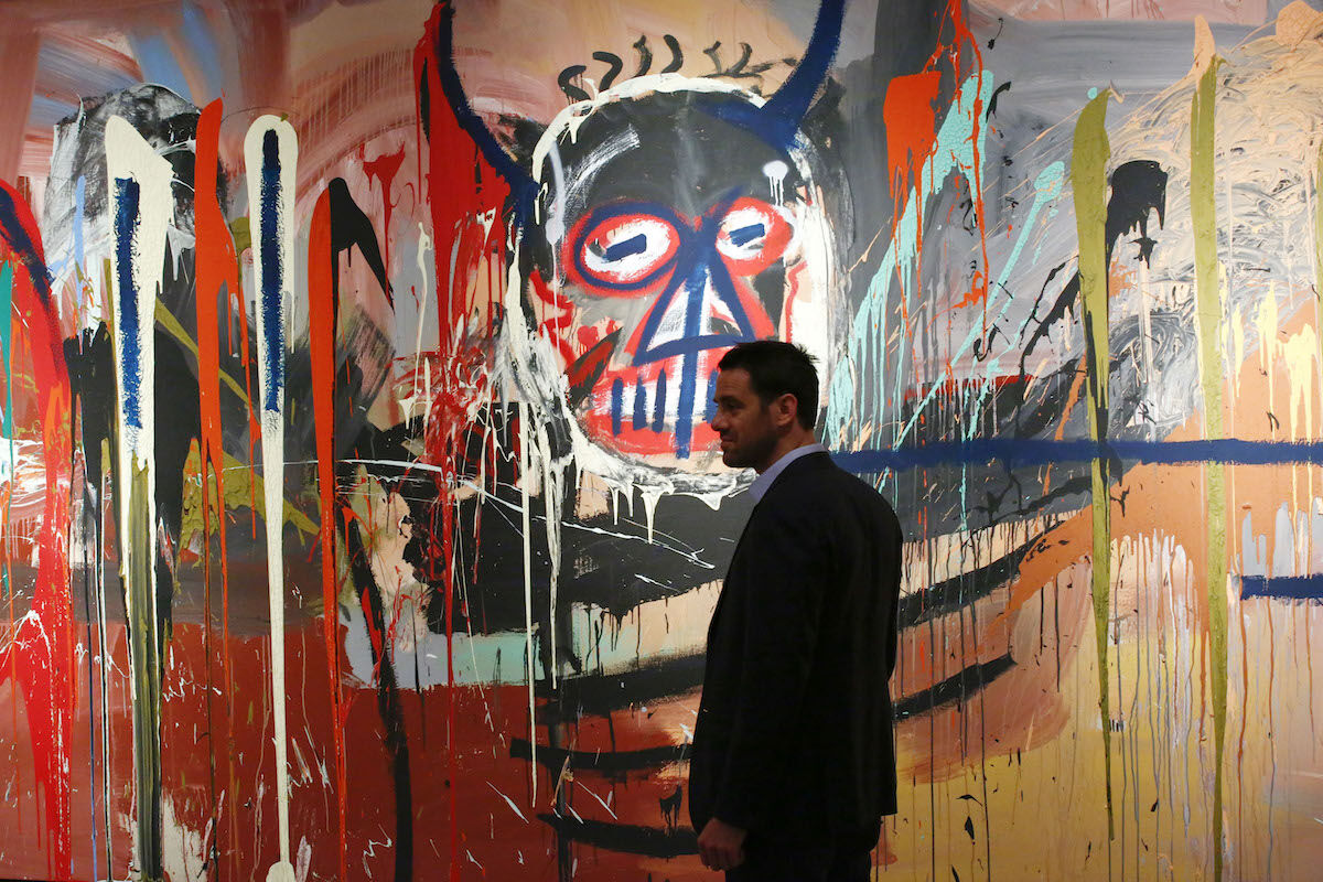 Loic Gouzer of Christie's standing next to an untitled painting by Jean-Michel Basquiat at a 2016 press preview of Christie's Contemporary, Impressionist, Modern, and Post-War Art in New York. Photo by Kena Betancur/AFP/Getty Images.