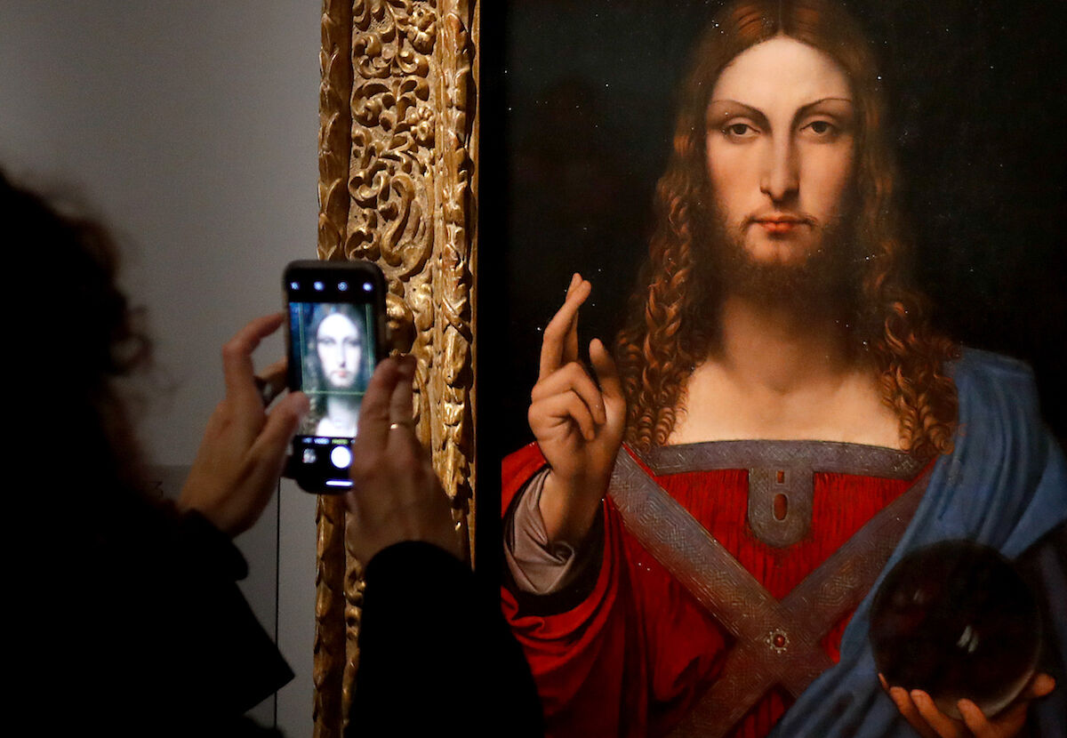 A visitor takes a photograph of a painting in the Leonardo da Vinci exhibition at the Louvre museum in Paris. Photo by François Guillot/AFP via Getty Images.