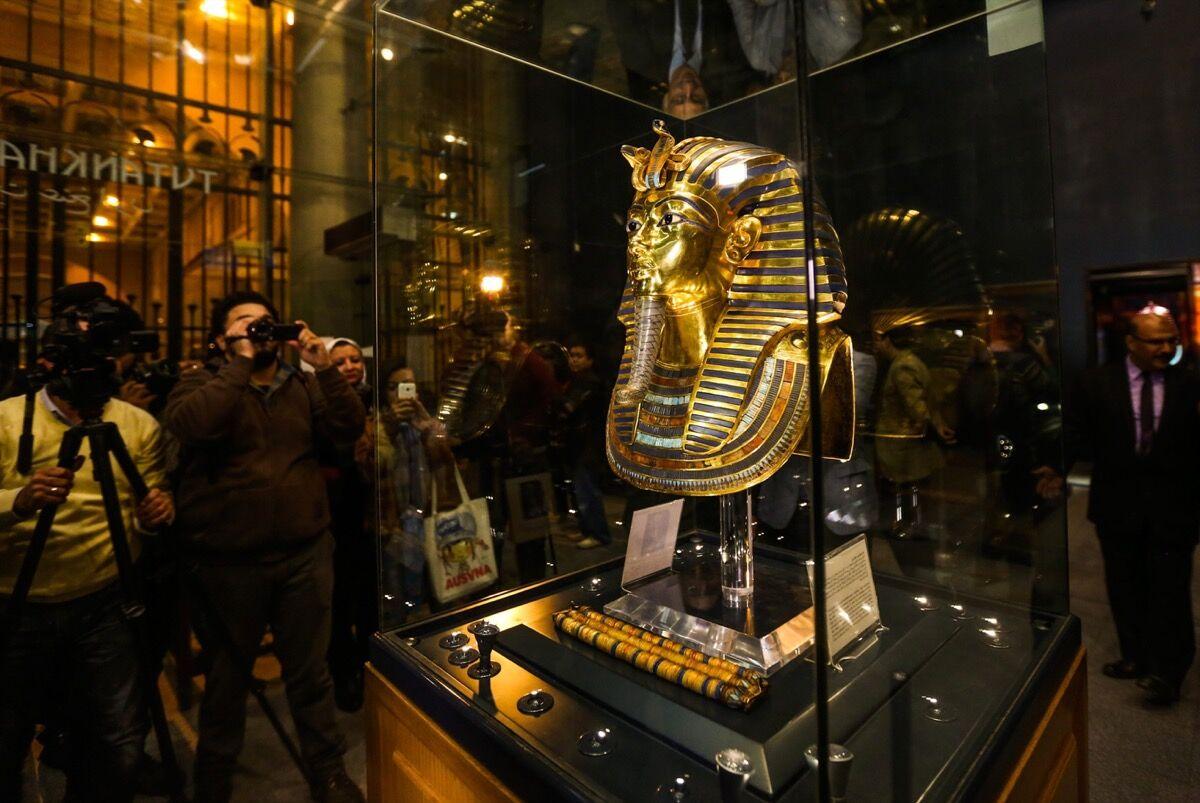 La máscara funeraria dorada del Rey Tutankamón en exhibición durante una ceremonia de inauguración en el Museo Egipcio, El Cairo, después de su proceso de restauración en 2015. Foto de Mostafa Elshemy / Agencia Anadolu / Getty Images.
