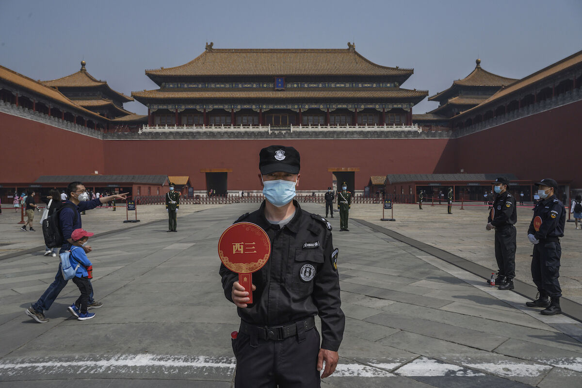 A guard wears a protective mask as he stands at the entrance to the Forbidden City as it re-opened to limited visitors or the May holiday, on May 1, 2020 in Beijing. Photo by Kevin Frayer/Getty Images.