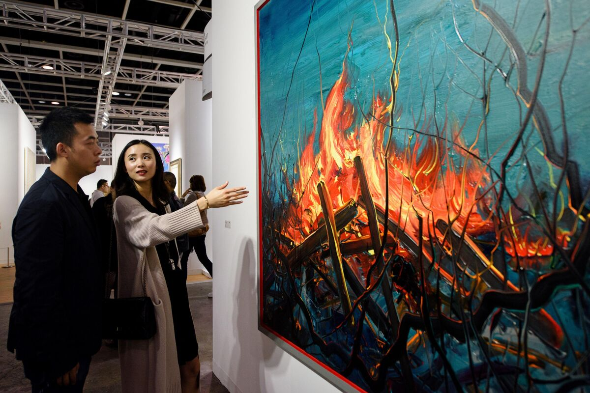 Investment banker Huang Xiaoshuai and his wife Wei Mengyuan chat in front of their newly acquired painting Fire by Chinese artist Zeng Fangzhi at Art Basel in Hong Kong. Photo by Anthony Wallace/AFP/Getty Images.