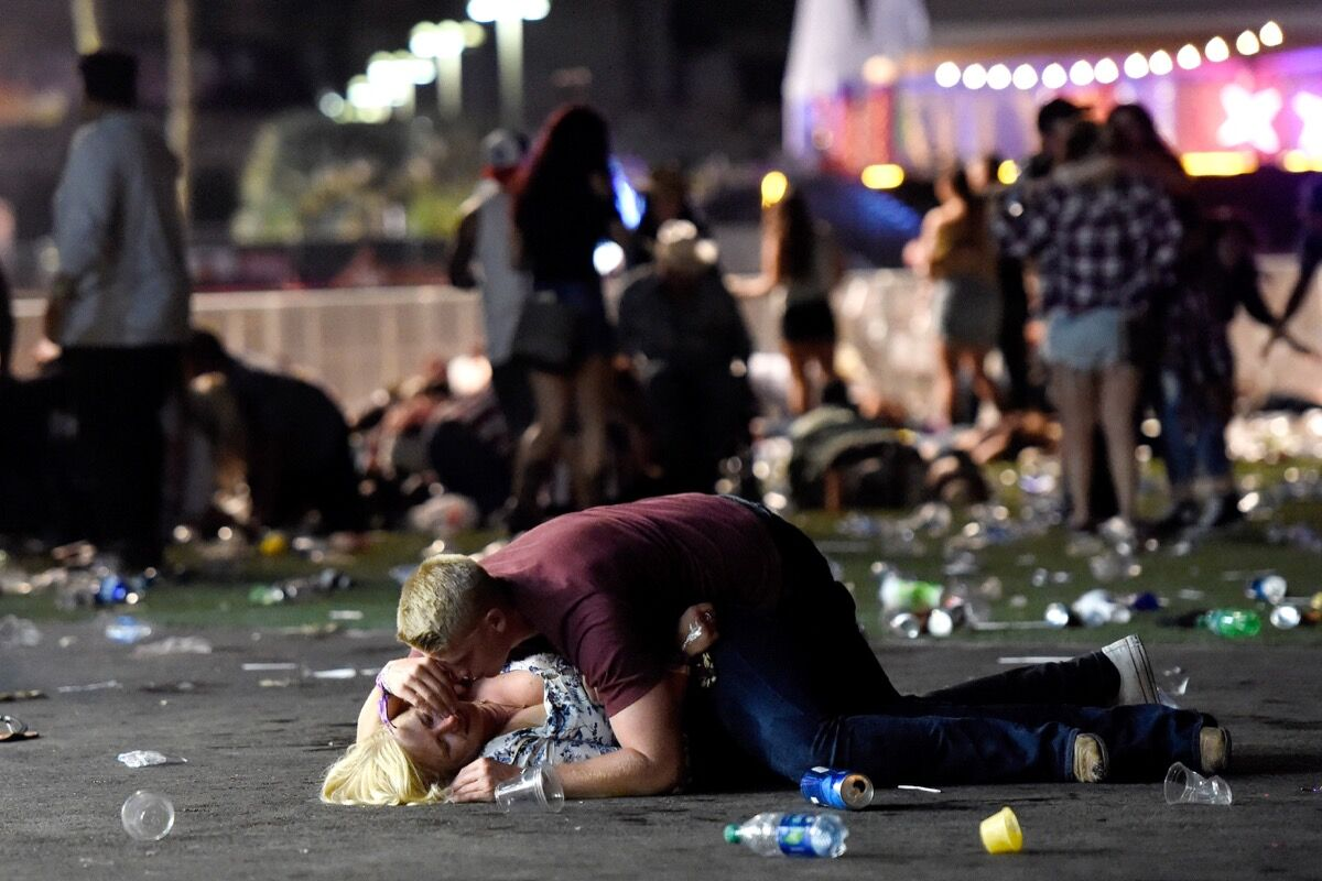 LAS VEGAS, NV - OCTOBER 01: A man lays on top of a woman as others flee the Route 91 Harvest country music festival grounds after a active shooter was reported on October 1, 2017 in Las Vegas, Nevada. A gunman has opened fire on a music festival in Las Vegas, leaving at least 2 people dead. Police have confirmed that one suspect has been shot. The investigation is ongoing. The photographer witnessed the man help the woman up and they walked away. Injuries are unknown. (Photo by David Becker/Getty Images)