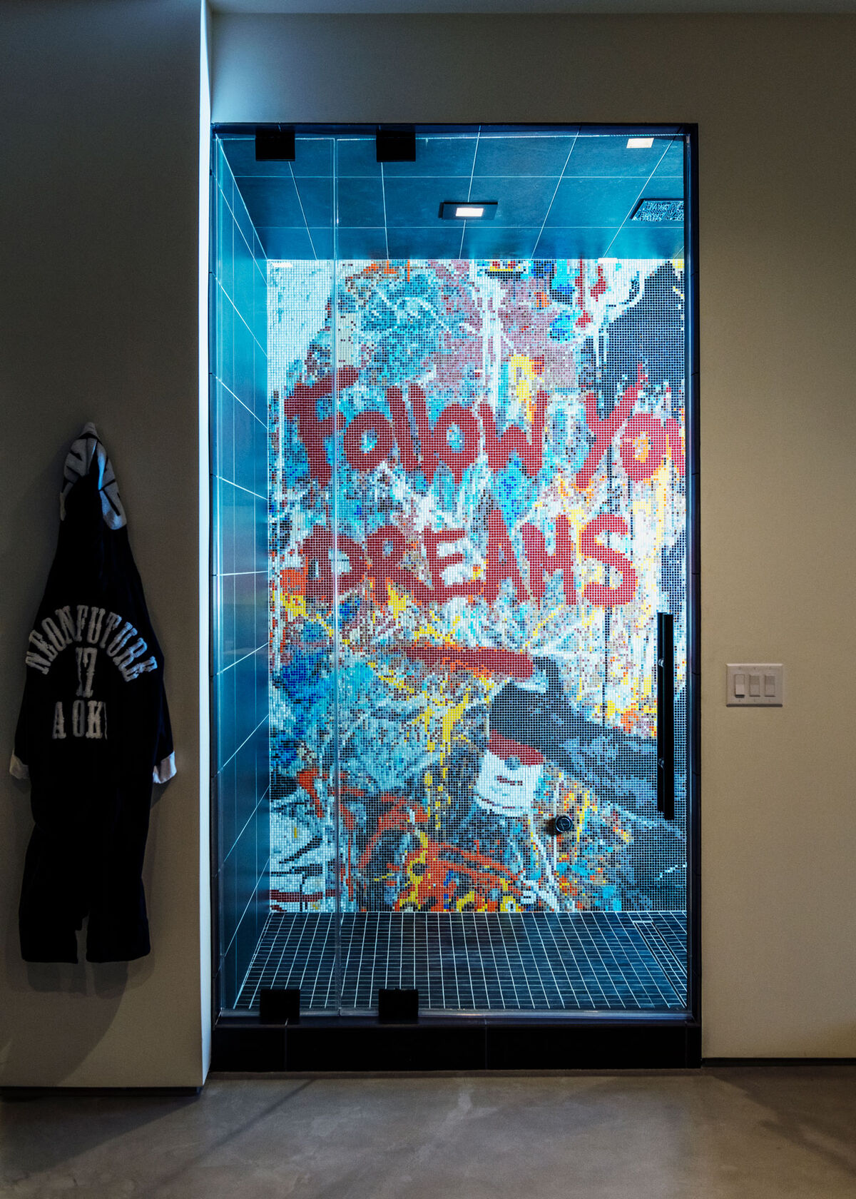 A bathrobe with the title of Aoki's Neon Future  trilogy of albums hangs next to a graffiti-covered shower. Photo by Brian Guido for Artsy.