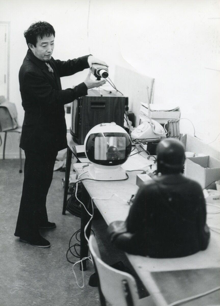 Nam June Paik installing TV-Buddha, 1974, in the Stedelijk Museum. Photo by Rene Block. Courtesy of Stedelijk Museum Amsterdam.
