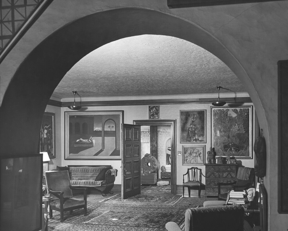 Living room and foyer viewed from the dining room, ca. 1944. Photo by Fred R. Dapprich. Courtesy of Philadelphia Museum of Art, Library and Archives, Arensberg Archives. Pictured artworks: Giorgio de Chirico, The Soothsayer's Recompense, 1913. © 2020 Artists Rights Society (ARS), New York / SIAE, Rome; Marcel Duchamp, The King and Queen Traversed by Swift Nudes at High Speed, 1912. © Association Marcel Duchamp / ADAGP, Paris / Artists Rights Society (ARS), New York 2020; Jean Metzinger, Landscape with Roofs, 1914. © 2020 Artists Rights Society (ARS), New York / ADAGP, Paris; Pablo Picasso, Female Nude, 1910. © 2020 Estate of Pablo Picasso / Artists Rights Society (ARS), New York.