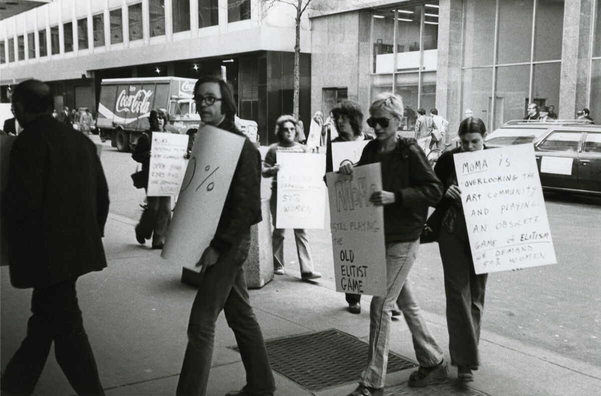 "Nancy Spero protesting outside of MoMA, 1976. Spero's sign reads, ""MoMA STILL PLAYING THE OLD ELITIST GAME."" Photo by Mary Beth Edelson. Courtesy of Galerie Lelong & Co."