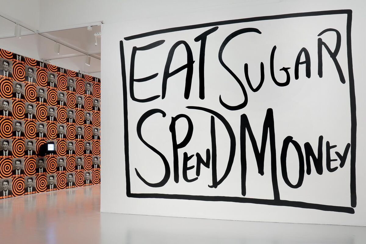 Installation view of Brand New: Art and Commodity in the 1980s at the Hirshhorn Museum and Sculpture Garden, 2018. Left to right: Gretchen Bender, Untitled (People with AIDS), 1986; Donald Moffett, He Kills Me, 1987; Jessica Diamond, T.V Telepathy (Black and White Version), 1989. Photo by Cathy Carver.