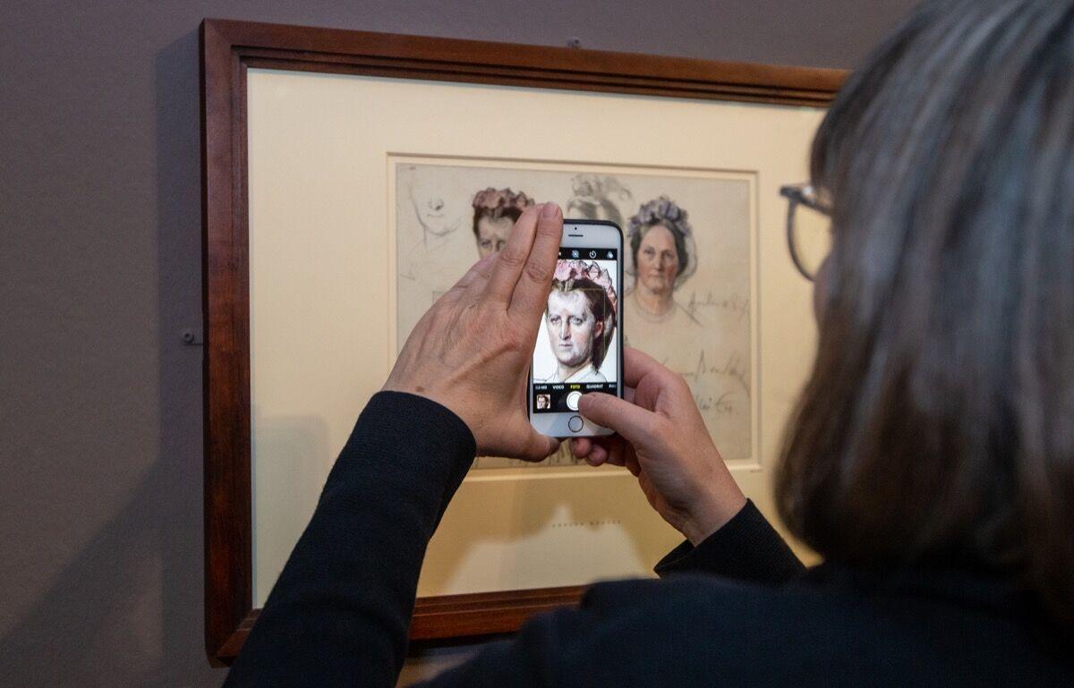 With a smartphone, a woman photographs Adolph Menzel's Fräulein von Below und Baroness von Schuckmann, 1864, in the Kupferstichkabinett. Photo by Andreas Gora/picture alliance. Image via Getty Images