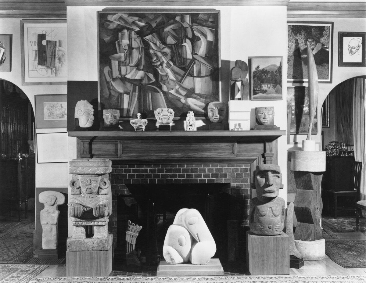 Living Room with views into the dining room through the north and south archways, ca. January 1951. Photo by Floyd Faxon. Courtesy of Philadelphia Museum of Art, Library and Archives, Arensberg Archives. Pictured artworks: Constantin Brancusi, Prodigal Son, 1914–15, and Three Penguins, 1911–12. © Succession Brancusi – All rights reserved (ARS) 2020; Georges Braque, Still Life (Violin), 1913, and Still Life (with the Word VIN), 1912–13. © 2020 Artists Rights Society (ARS), New York / ADAGP, Paris; Marcel Duchamp, The King and Queen Surrounded by Swift Nudes, 1912, and Yvonne and Magdeleine Torn in Tatters, 1911. © Association Marcel Duchamp / ADAGP, Paris / Artists Rights Society (ARS), New York 2020; Paul Klee, Village Carnival, 1926. © 2020 Artists Rights Society (ARS), New York; Pablo Picasso, Old Woman (Woman with Gloves), 1901, and Head, 1906. © 2020 Estate of Pablo Picasso / Artists Rights Society (ARS), New York.