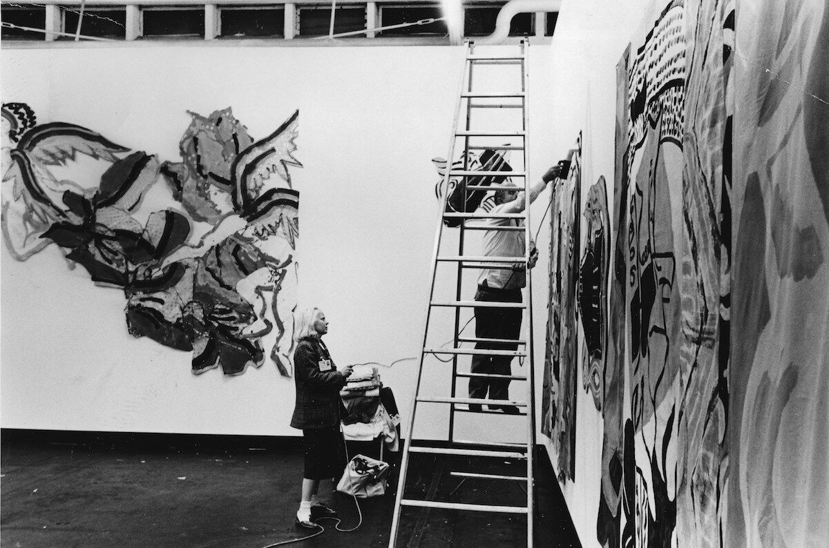 Holly Solomon hanging work by Robert Kushner at the Holly Solomon Gallery, 1981. Courtesy of Thomas Solomon.