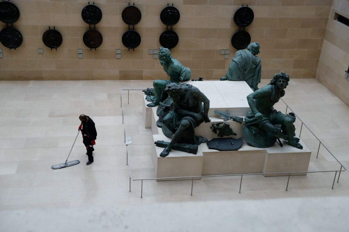 An employee walks next to Martin Desjardins's Quatre Captifs in the Musee du Louvre, Paris, closed to the public indefinitely amid concerns on the COVID-19 outbreak, 2020. Photo by Thomas Samson/AFP via Getty Images.