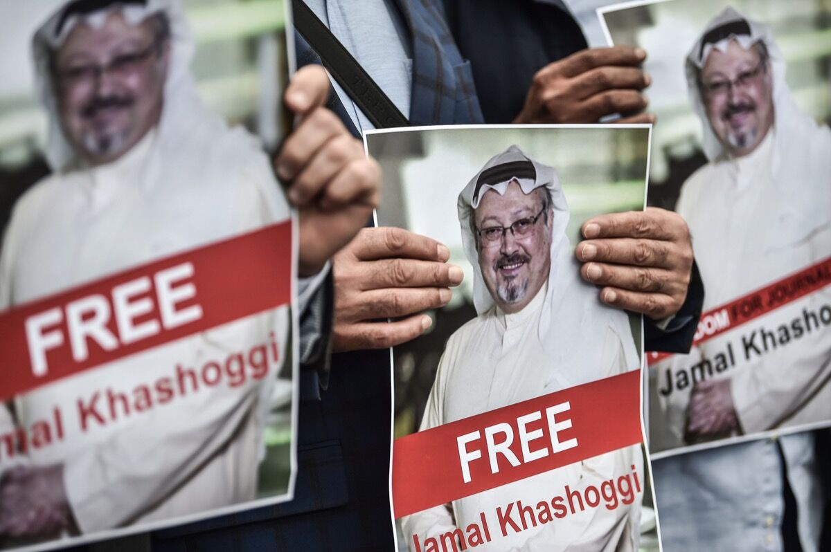 Protestors hold pictures of missing journalist Jamal Khashoggi during a demonstration in front of the Saudi Arabian consulate. Photo by OZAN KOSE/AFP/Getty Images.