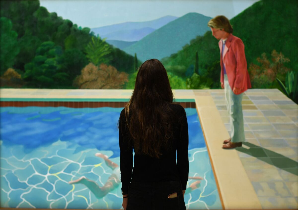 A woman views David Hockney, Portrait of an Artist (Pool with Two Figures), at Christie's, New York, 2018. Photo by Timothy A. Clary/Getty Images.