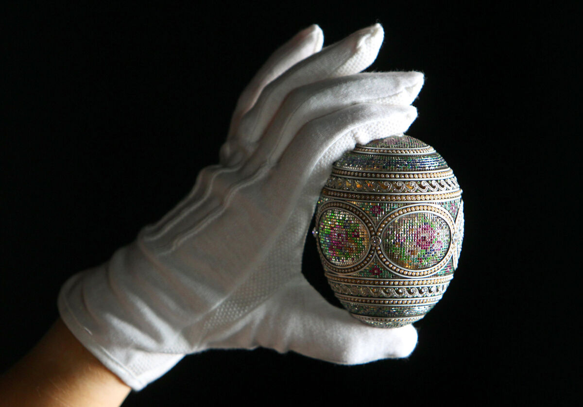 A curator from the Royal Collection examines a mosaic egg, made by Russian jeweller and goldsmith Peter Carl Faberge which was originally commissioned by Tsar Nicholas II in 1914 and acquired by Queen Mary in 1933. Photo by Dominic Lipinski/PA Images via Getty Images.