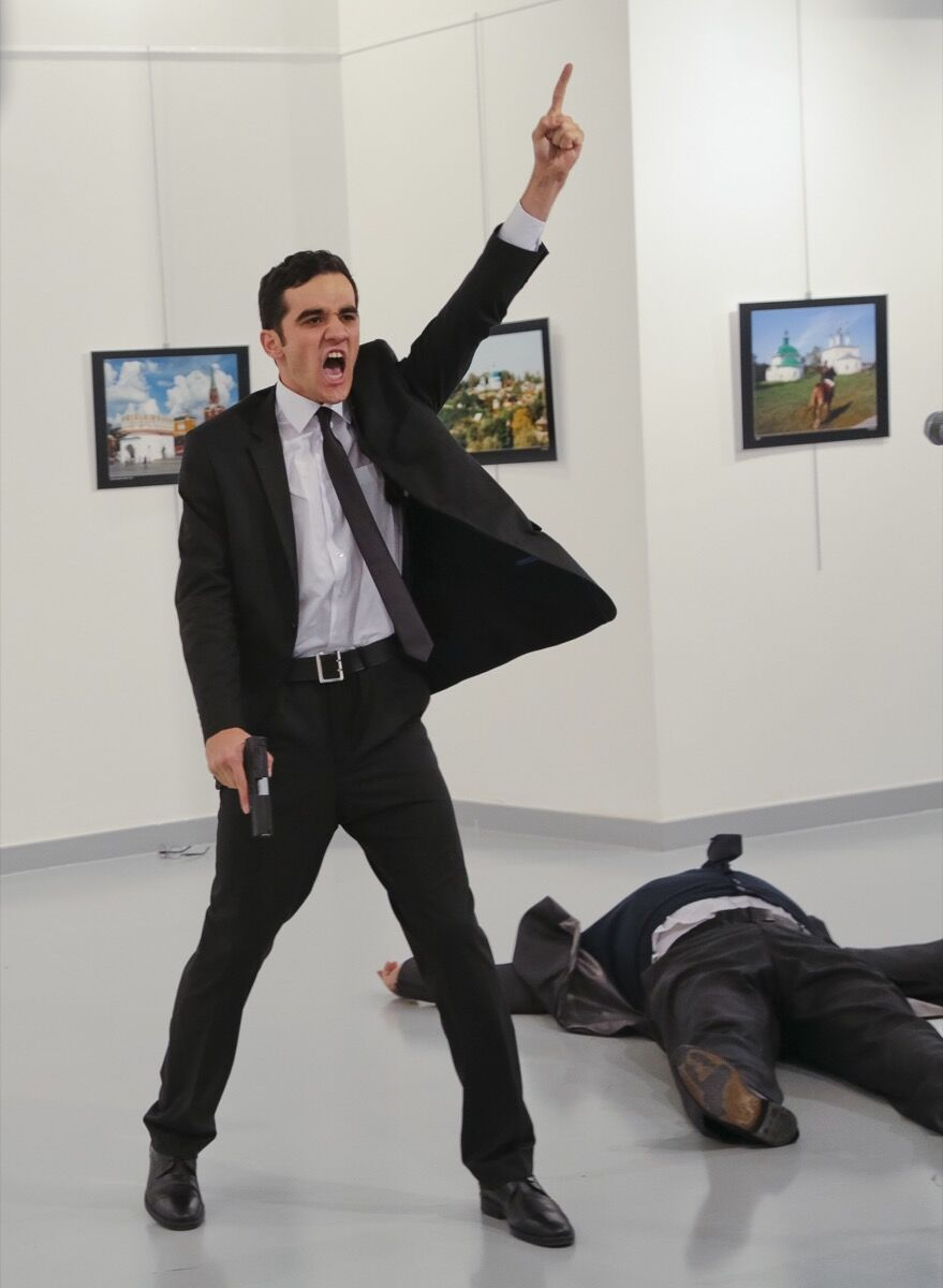 An unnamed gunman gestures after shooting the Russian Ambassador to Turkey, Andrei Karlov, at a photo gallery in Ankara, Turkey, Monday, Dec. 19, 2016. A gunman opened fire on Russia's ambassador to Turkey at a photo exhibition on Monday. The Russian foreign ministry spokeswoman said he was hospitalized with a gunshot wound. (AP Photo/Burhan Ozbilici)