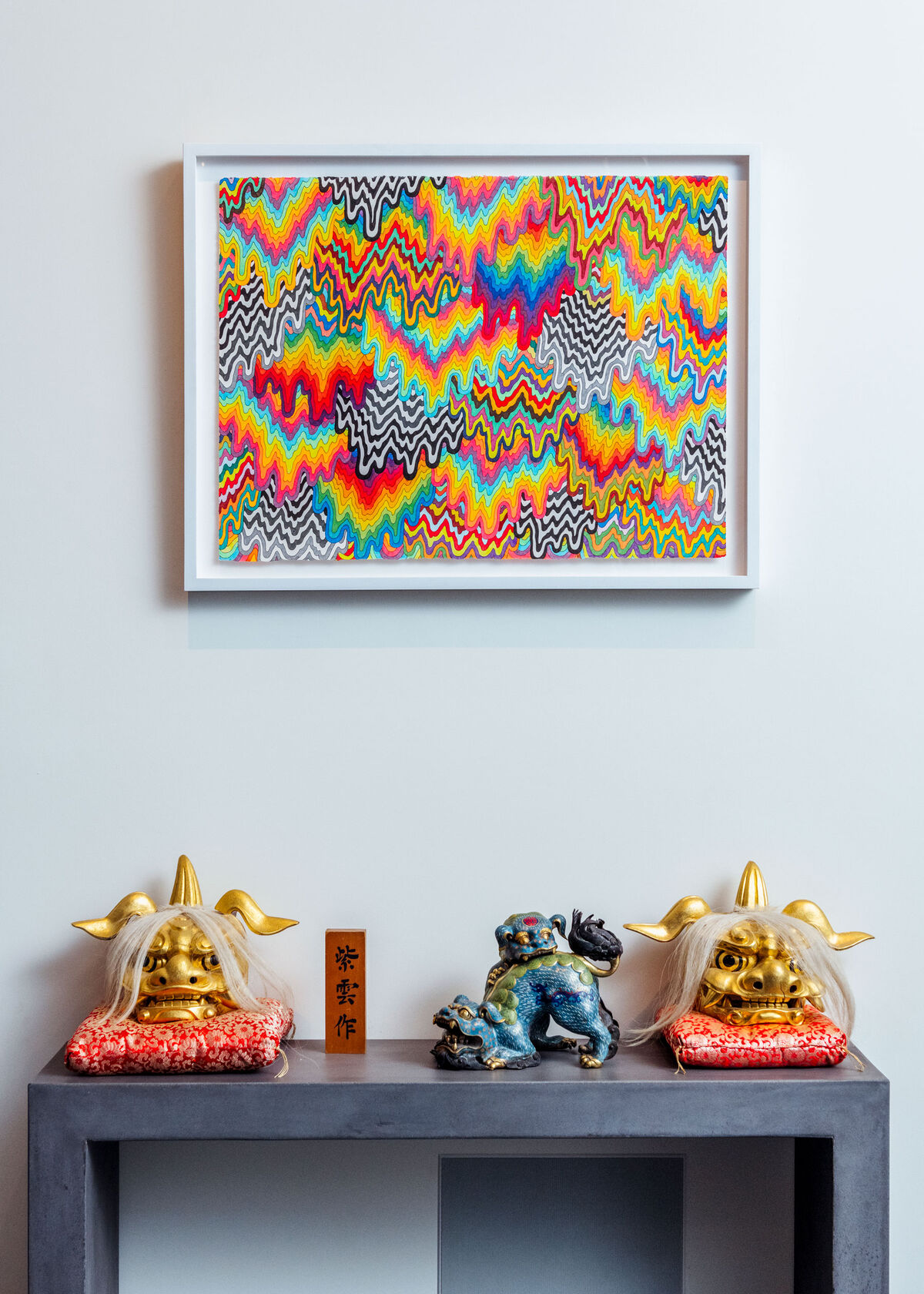 An artwork by Jen Stark hangs above a selection of sculptures. Photo by Brian Guido for Artsy.
