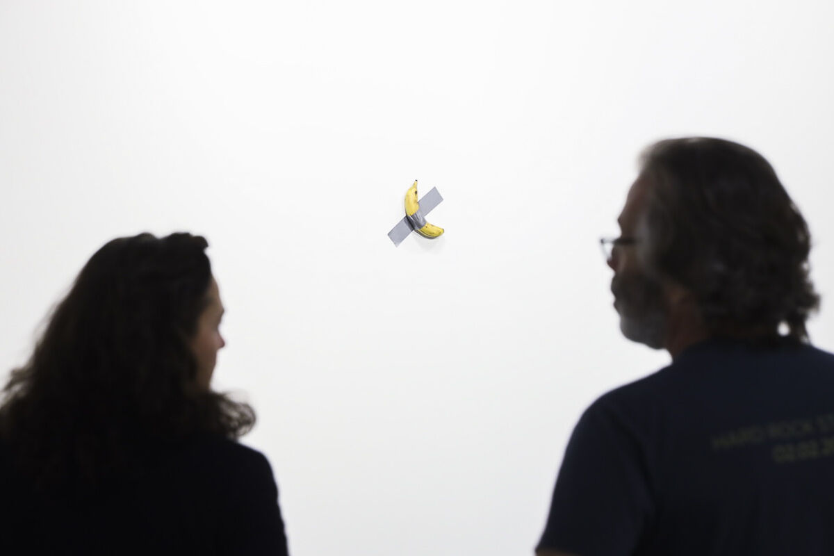 Visitors contemplate Comedian (2019) by Maurizio Cattelan at the 2019 edition of Art Basel in Miami Beach. Courtesy Art Basel.