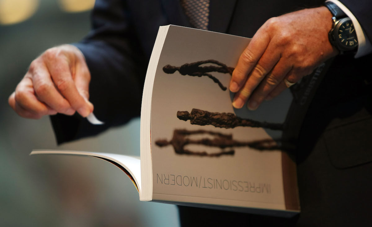 A guest holds a catalog before entering a Christie's sale in New York. Photo by Mario Tama/Getty Images.