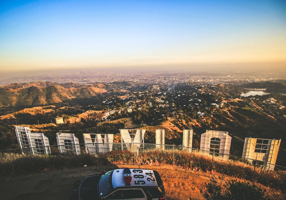 A police car parked near the Hollywood sign. Photo by Florian Wehde on Unsplash.