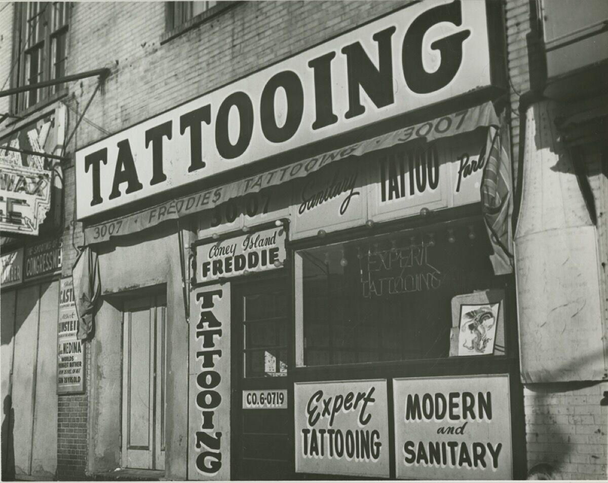 """Irving Herzberg, Tattoo shop of """"Coney Island Freddie"""" just prior to New York City's ban on tattooing, 1961. Courtesy of Brooklyn Public Library. Image courtesy of New York Historical Society."""