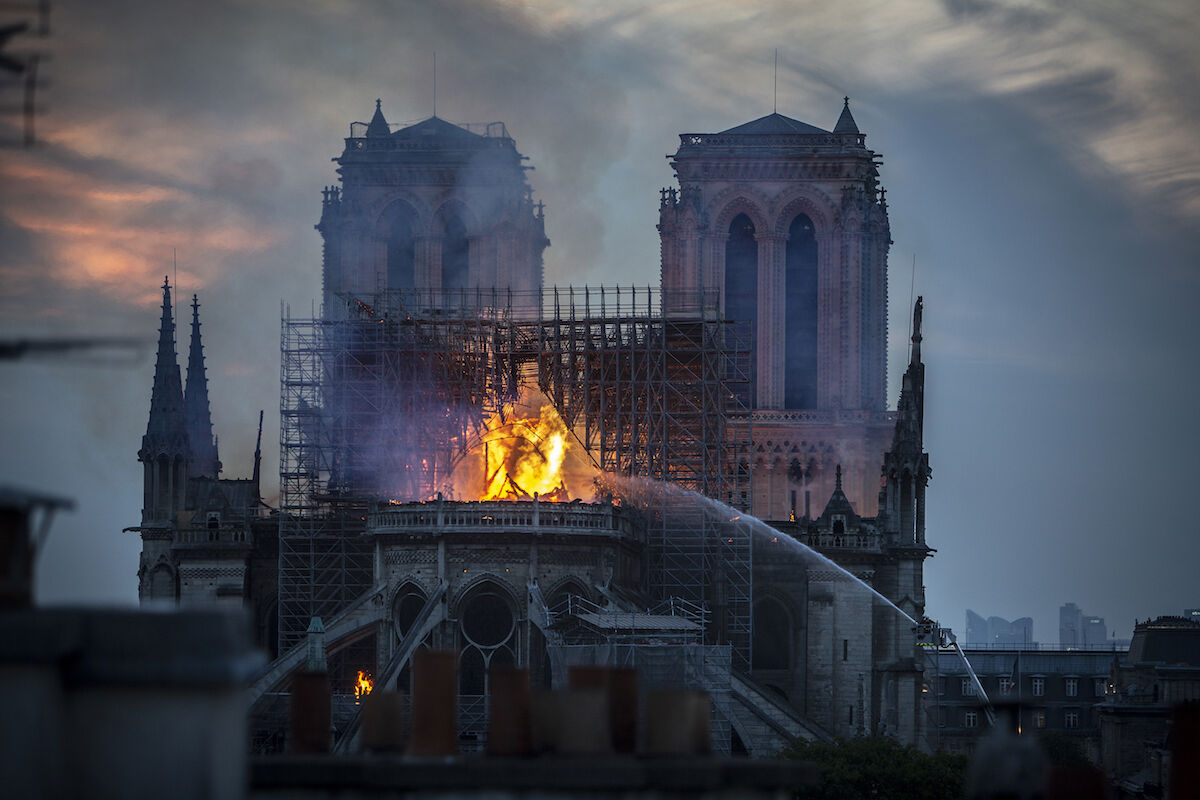 A devastating fire raged inside Notre Dame Cathedral in Paris as the sky darkened on April 15, 2019. Photo by Veronique de Viguerie/Getty Images.