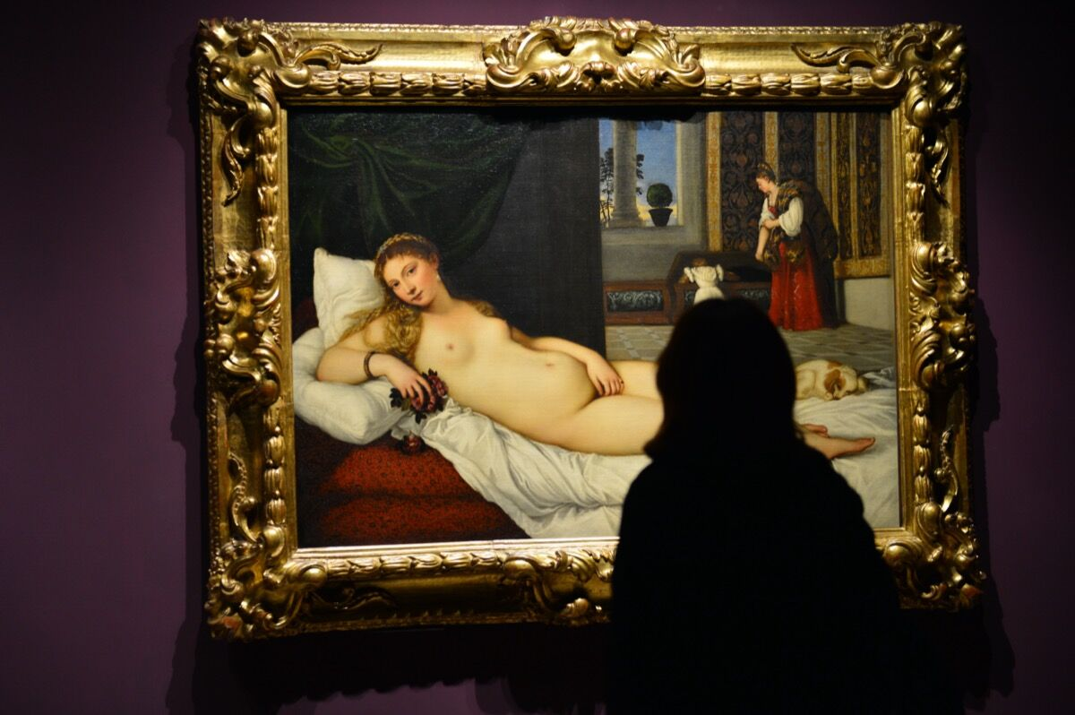 A woman looks at Titan's Venus of Urbino at the Doge's Palace in Venice. Photo by Giuseppe Cacace/AFP. Image via Getty Images.