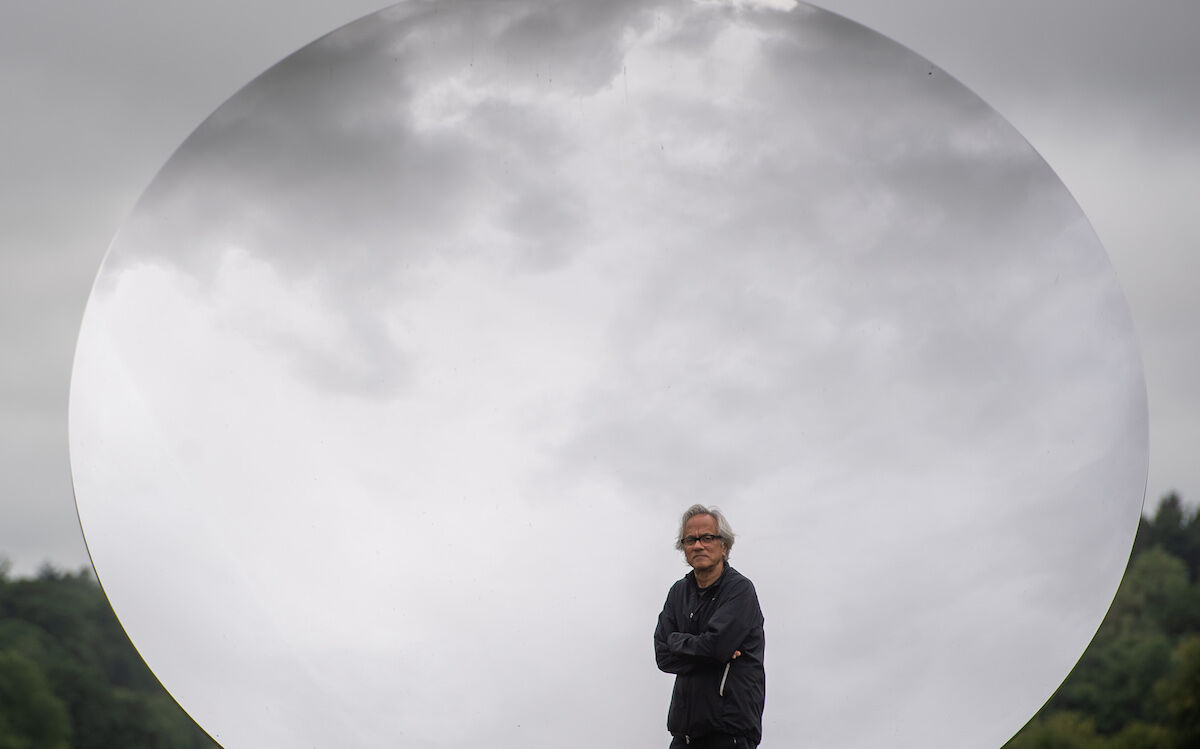 Anish Kapoor in front of his sculpture Sky Mirror at Houghton Hall in the United Kingdom. Photo by Joe Giddens/PA Images via Getty Images.
