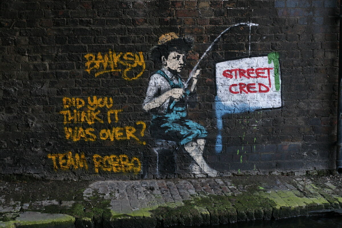 A Banksy mural altered by Mr. Robbo. Photo by Bob Bob, via Wikimedia Commons.