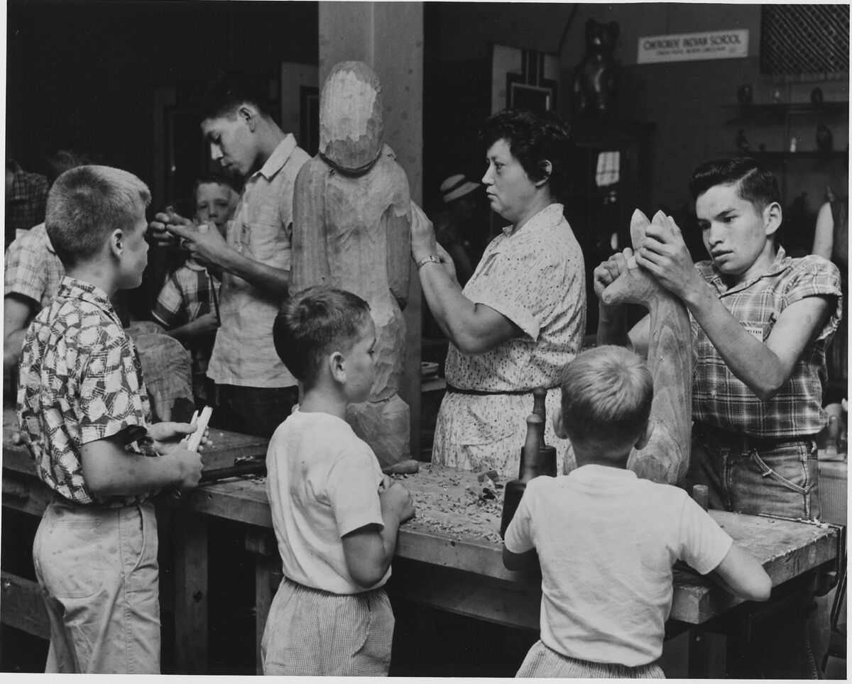 Visitors to the Craftsmen's Fair at the Cherokee Indian Reservation, Cherokee North Carolina, watch Amanda Crowe, well-known Cherokee wood sculptor and her students demonstrate their art. Courtesy of the National Archives and Records Administration, via Wikimedia.