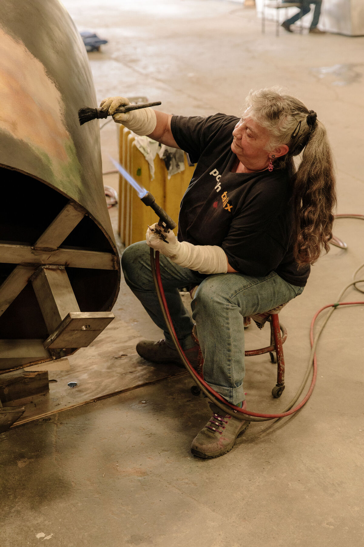 Rosemary Rednour is applying hot patina to a sculpture by Jim Sardonis. Photo by Ricky Rhodes for Artsy.