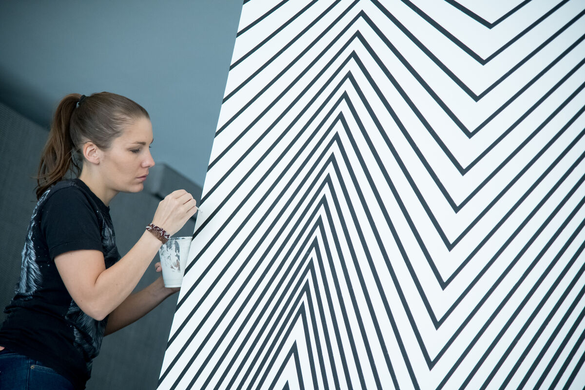 Claudia Comte installing Electric Burst (Lines and Zigzags) , 2018, at the Contemporary Art Museum St. Louis. Photo by Jon Gitchoff. Courtesy of the Contemporary Art Museum St. Louis.