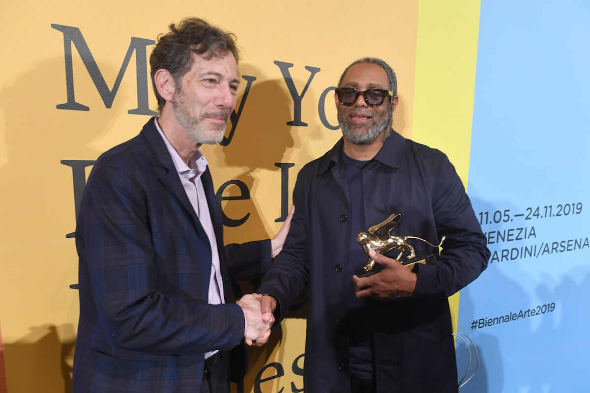 Arthur Jafa and Ralph Rugoff at the 2019 Venice Biennale Golden Lions ceremony. Photo by Felix Hörhager/picture alliance via Getty Images.
